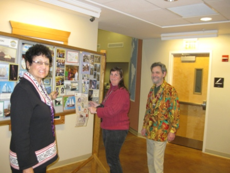 Programming Committee chair Laura Pires-Hester and volunteers Annie McDowell and Chuck Smiler prepare the Ernestina history display