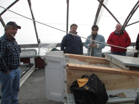 Manny Silva, Karl Pastore, Commissioners Laura Pires-Hester and Steve Walsh examine the progress on repairs to the fish hold hatch.