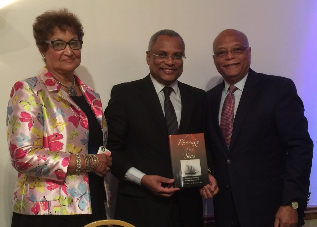 "Commission Chair Laura Pires-Hester and SEMA President Julius Britto presented the Prime Minister with a copy of the new book ""Phoenix of the Seas"""