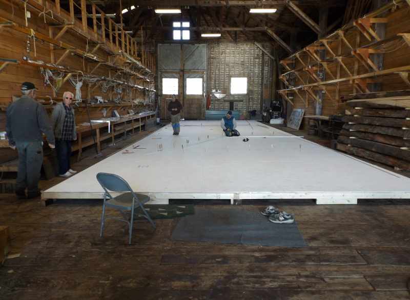 A lofting table has been set up inside to lay out the ship's plans.