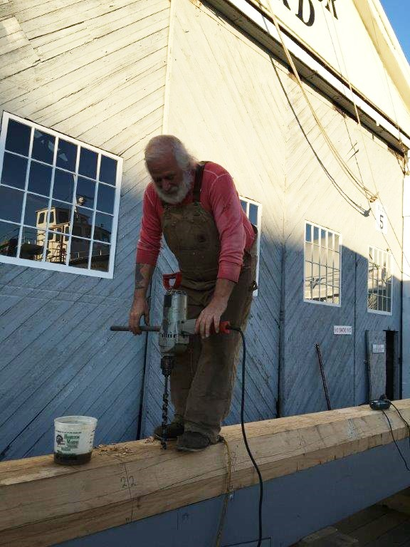 Shipwright Rob Stevens is drilling holes for the alignment bolts