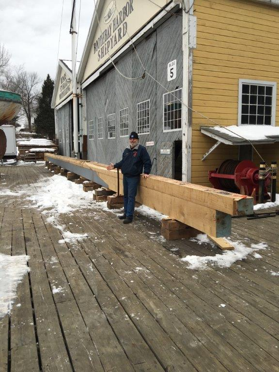 Capt. Dave Thompson standing next to the aft section of the new keel for scale.  The grey part is the four sections of lead ballast.   The ends of the keel will be faired into the hull.