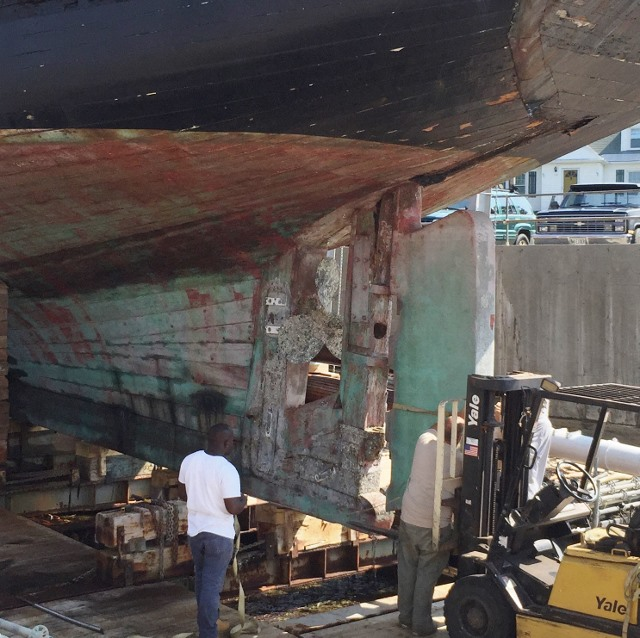 The workers here were removing the rudder in July, 2015.  The rudder is at the right.  You can see the rudder shaft going up into the passage in the rudder post. rudder post supports the rudder.  In the space to the left of the rudder post you can see the three blades of the propeller and the stern post running up from the keel into the hull.