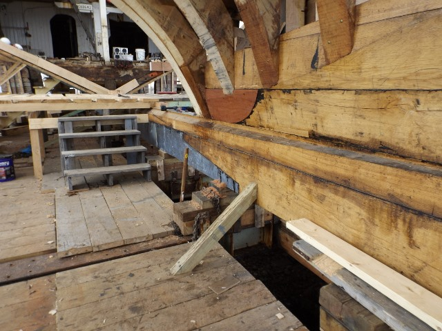 The new keel looking forward.  The grey scarfed section is one of the lead ballast sections.  The keel is beveled to receive the garboard.  The right side shows the dead wood with the stern frames attached.  At the upper left you can see into the forward section of the ship.  Between is a temporary platform to support the construction process.