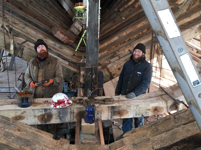The crew is getting the frame ready to raise,  Notice the jack and timber holding up the deck.