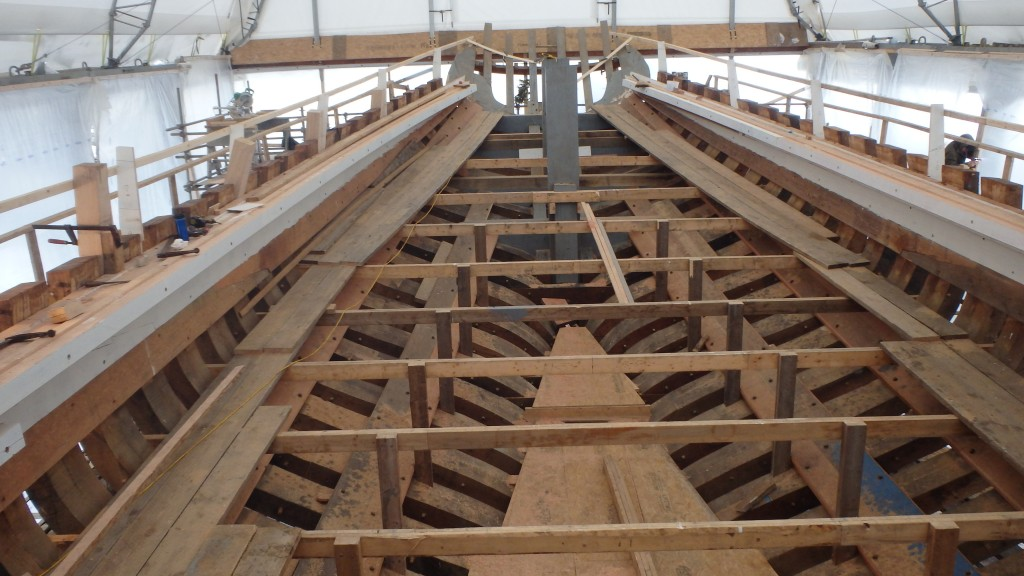 "Besides the sheer clamps along the top of the frame you can see the stringers which add stability to the frame.  There is a lot of temporary structure here, including the staging, the horizontal supports, and the plywood ""sole"" over the floor timbers."
