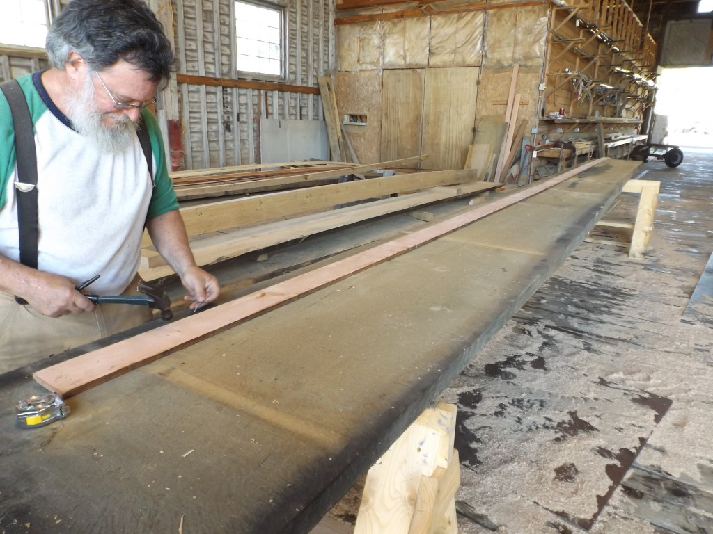 The 3 inch thick plank is marked and cut. Here a spiling batten is used to mark the curve needed for this plank.