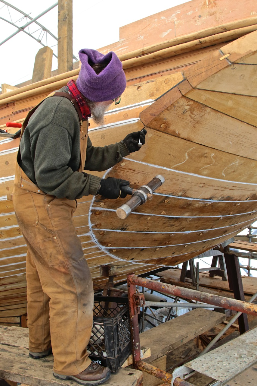 Here the last bit of the transom is being caulked. The lower planks already have the finishing seam compound. credit Robert Mitchell