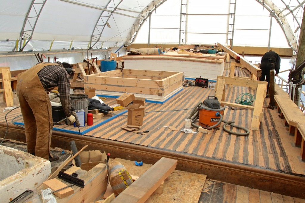 The new Douglas fir aft deck is sealed.  Now the sealant is being applied where the planking meets the break in the deck which steps down to the foredeck. The platform masked in blue is where the opening for the main mast will pass through to the mast step on the keel. credit Robert Mitchell