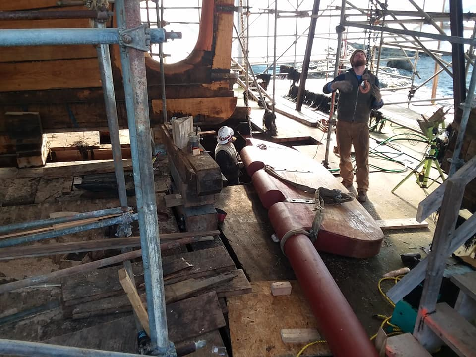 The crew is getting ready  to lift the rudder into place.  They give scale to the size of the rudder.  You can see two of the gudgeons on the prick post ready to receive the three pintles. credit North Atlantic Shipbuilding & Repair