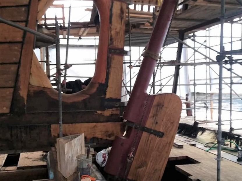It's a hard-hat job as the chains and straps lift the rudder into place. The top of the rudder postwill be lined up to enter the shaft and then the rudder is listed into place. credit North Atlantic Shipbuilding & Repair
