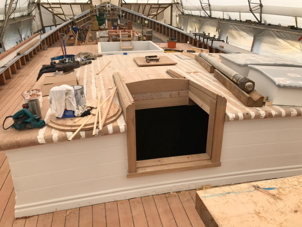 Working on framing for aft cabin companionway and caulking cabin top. credit Dave Thompson