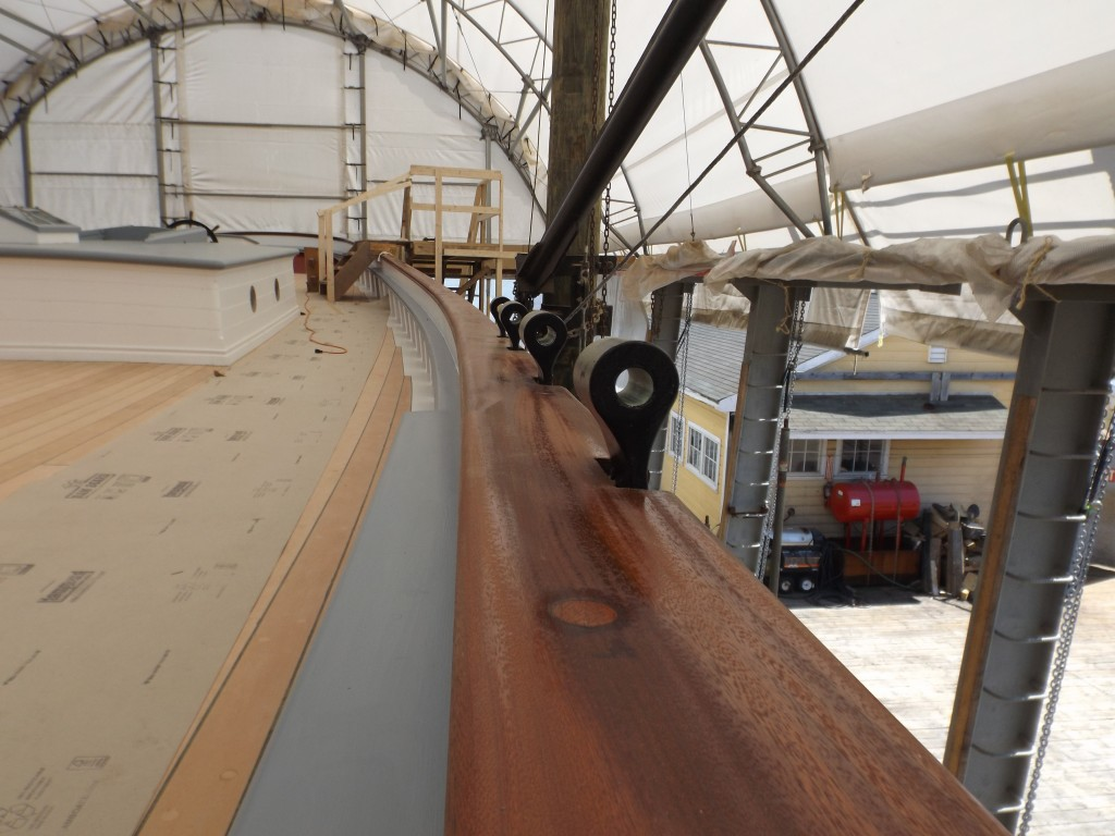 Port side, looking aft, the pin rail and tops of the chain plates for the main mast shrouds.
