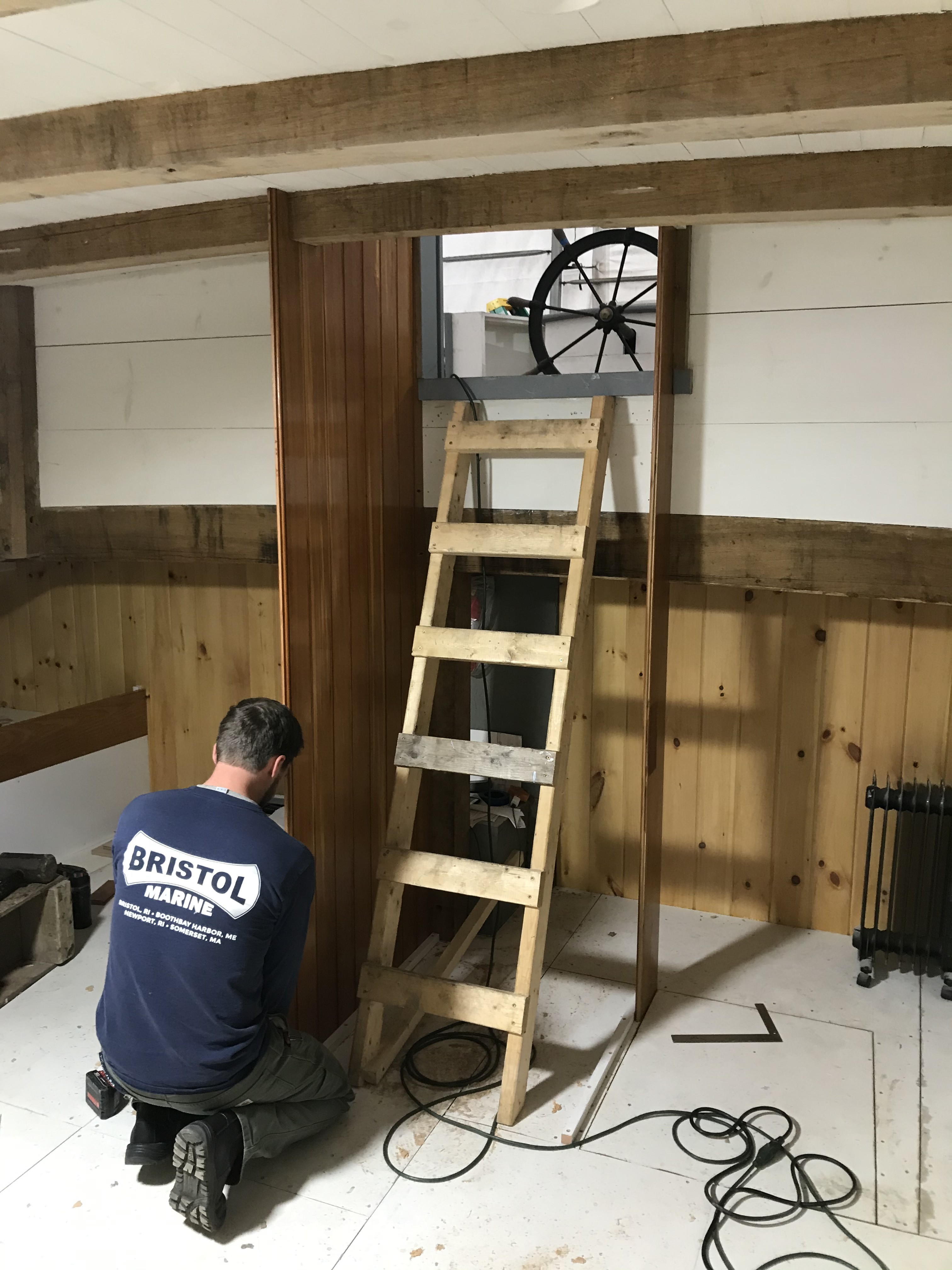 David Thorpe is seen here fitting tongue and groove paneling that will serve as the frame for a companionway ladder into the aft cabin from the deck.  You can see the original steering wheel from 1894 in the background.
