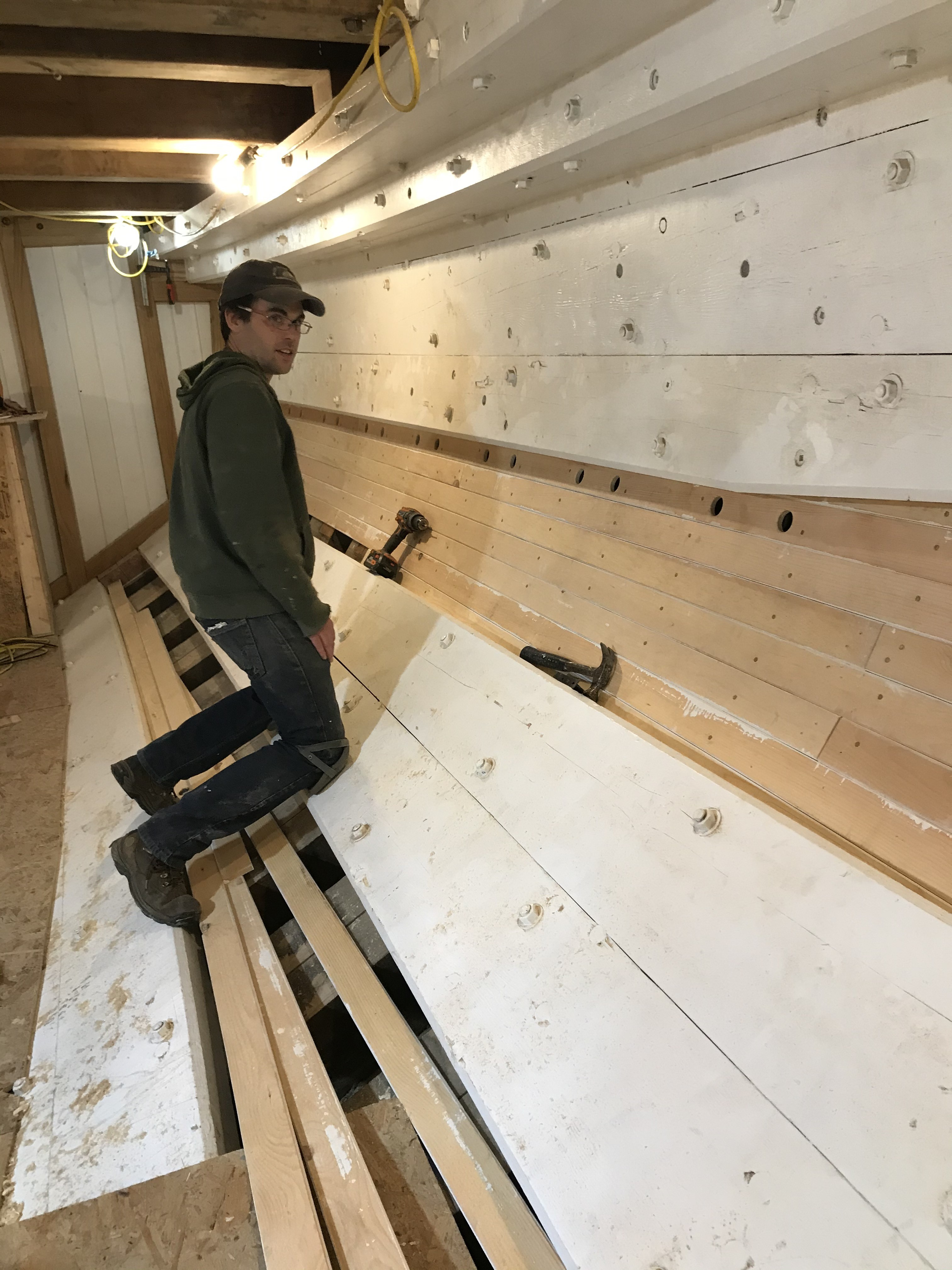 "In the Main Cabin, where accommodation installations will begin soon, work is underway preparing for the final fit-out.  Sam is seen here working on the interior ""light-ceiling"". This inner planking is installed to isolate the hull planking and frames from the interior spaces.  Ventilation holes are included across the top edge to ensure that air can freely flow between the ""ceiling"" and the hull to help keep the wood from deteriorating over time.  All of the vertical partitions that create bunks, cabinets, and lockers will be built directly to this surface in the coming weeks."