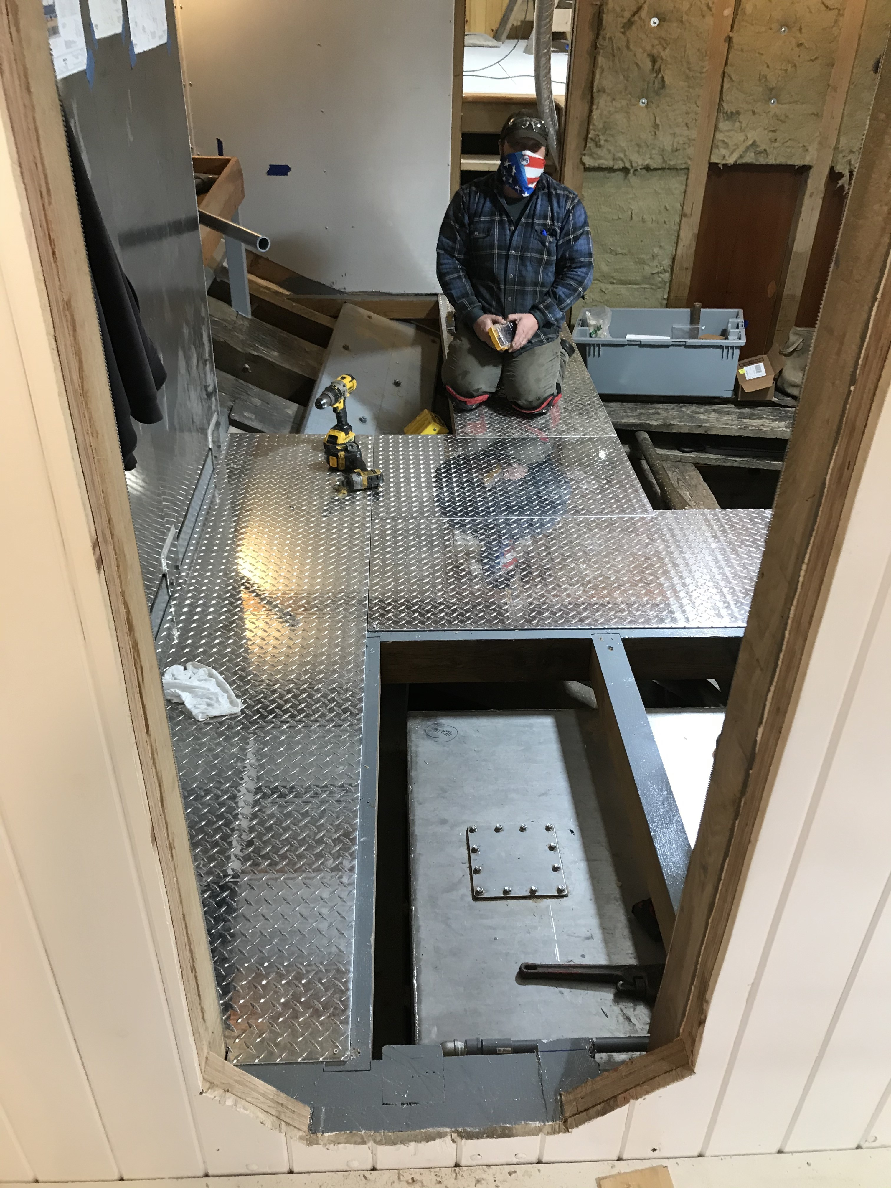 Jason Brassard is hard at work here installing the diamond plate flooring in the engine room.  Each piece of high-quality aluminum flooring is custom fitted according to the spacing and arrangement of the sole beams that run athwartship.  Special consideration is also given to maintenance and regular use of the ship's systems.  Certain pieces of this plate flooring will be conveniently secured to allow for quick lift out access to machinery spaces that will exist below the floor level