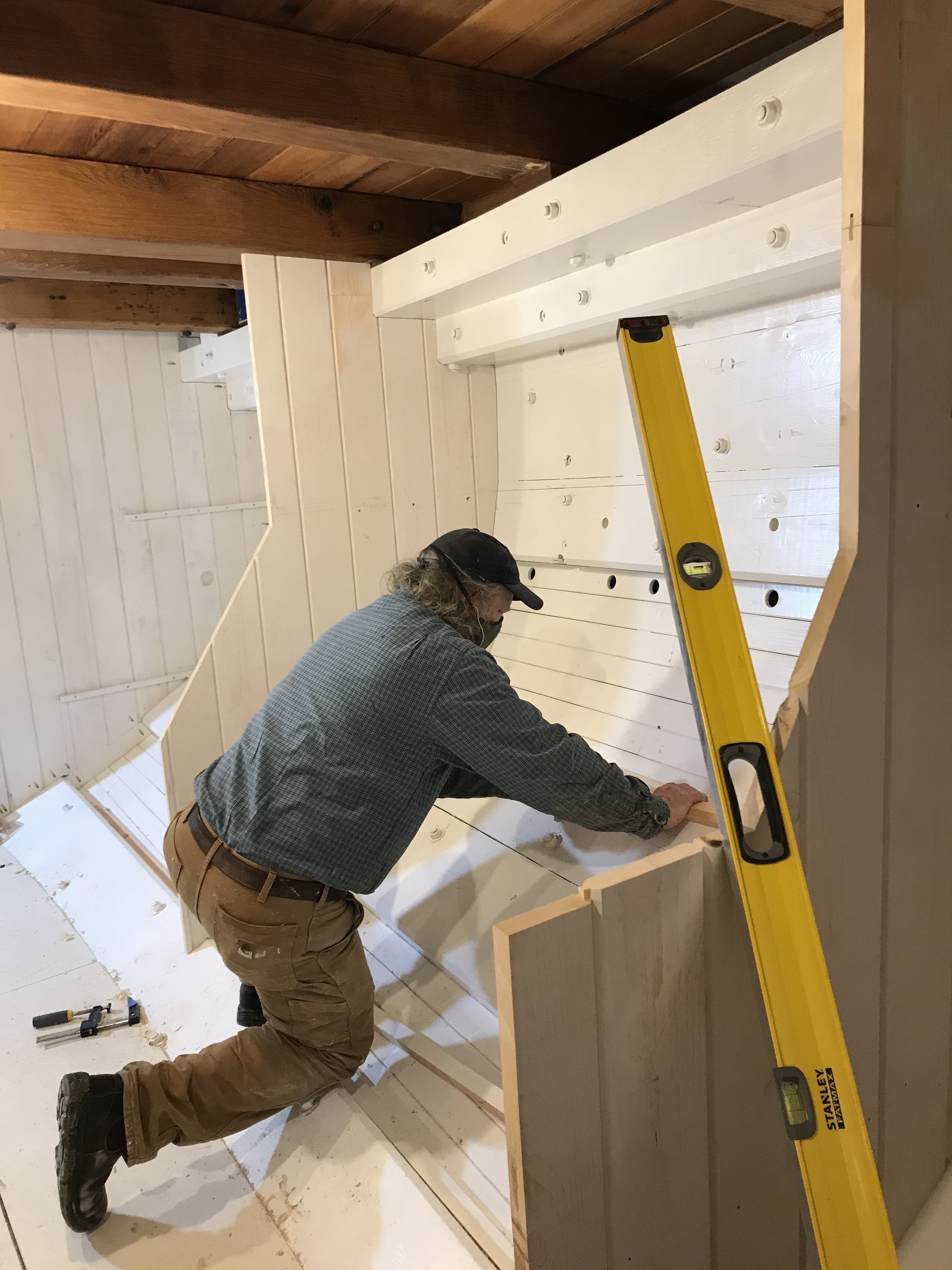 Tom Gerhardt is carefully laying out the positioning of outboard cleats that will be used to support bunks along the port side of the Main Cabin.