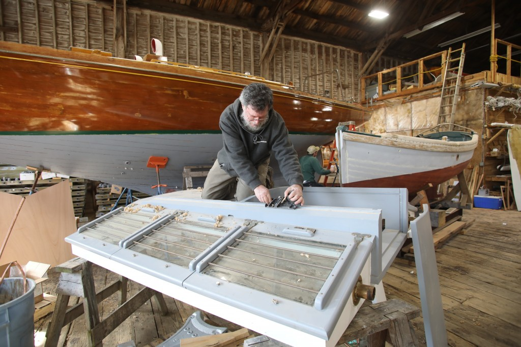 Fitting Hardware Our lead Shipwright David Short is finishing a detailed installation of the sliding hatchway for the Engine Room deck house.  Just a few hardware details are all that remain for the three primary deck houses.  We welcome the warmer weather for exterior projects like this. Photo Credit:  Robert Mitchell of Mitchell Photography