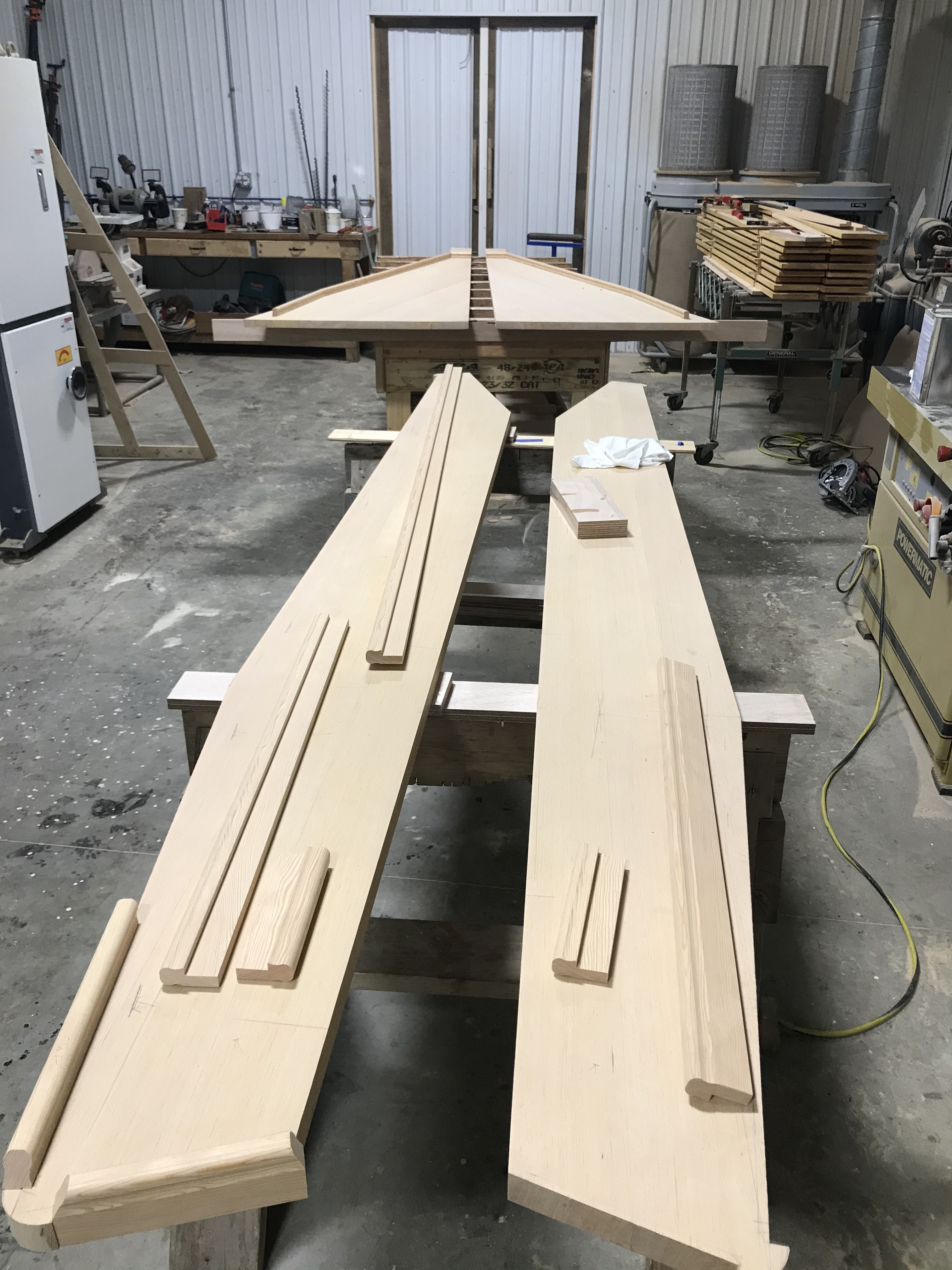 This table is coming together beautifully.  It is being built of Douglas Fir and is constructed to match the same profile and area of the original table.  In the foreground you can see the folding leaves being prepared for fiddles, and the fixed portion of the table is in the background.