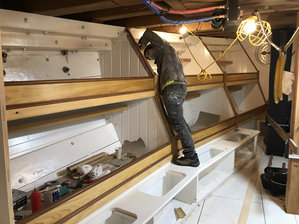 Kevin Danfelser is carefully painting around the final pieces of trim being installed along the bunks in the Foc'sle.  The trim is all being built in Oak and Mahogany.