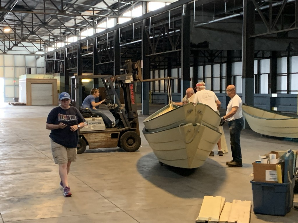 Melissa, Tiffany, Joe, Fred and Julius prepare to lift a dory with the fork lift and bring it to the elevator.