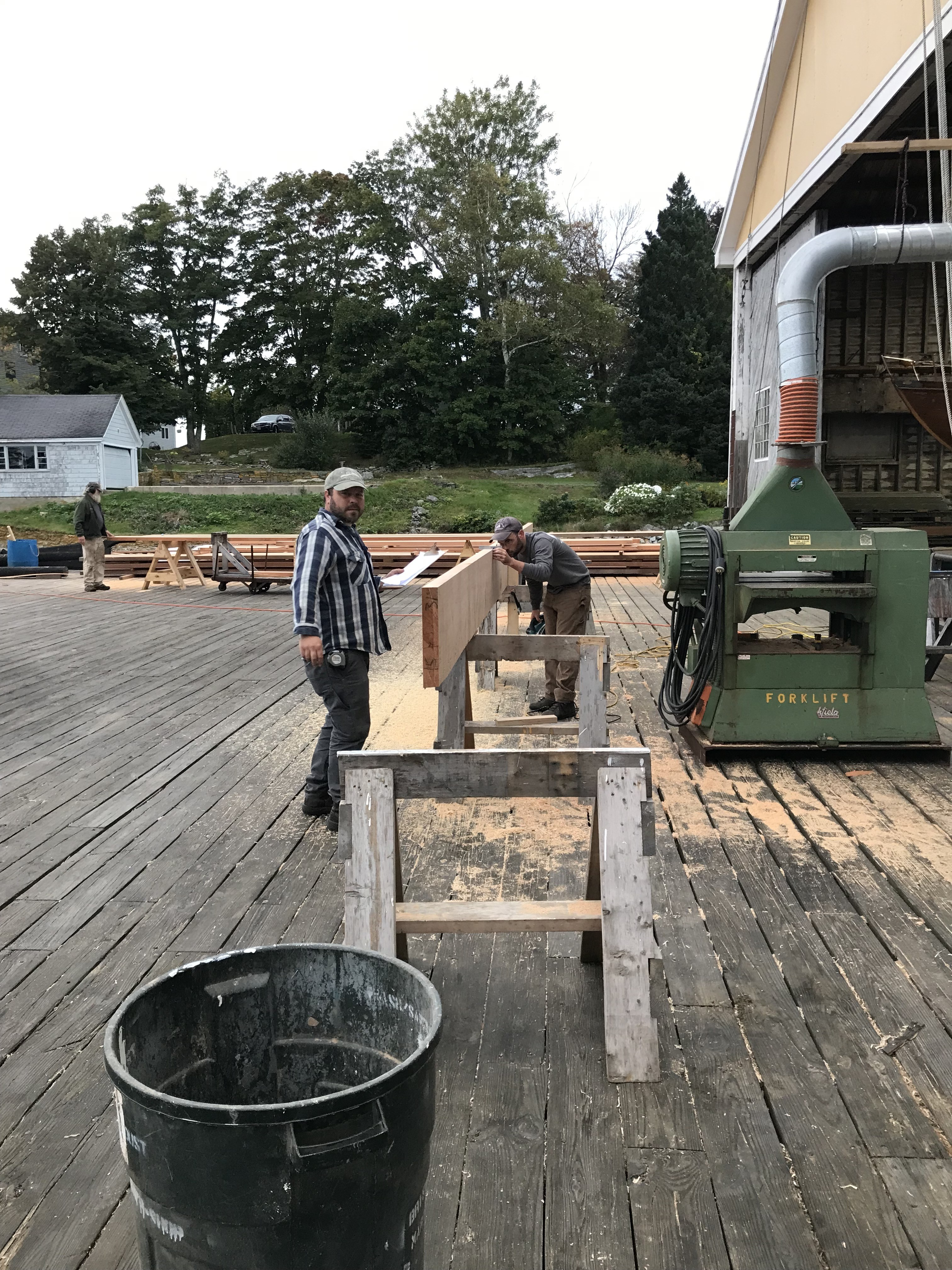 Jason and Sam Perkins are working together using the planer to bring raw lumber into specific thicknesses and widths necessary for the lamination process.  Each board is numbered and is marked to fit into a particular spar in a particular spot.  This lamination plan requires absolute accuracy in the preparation of each piece of lumber to ensure that the finished product meets required dimensions.